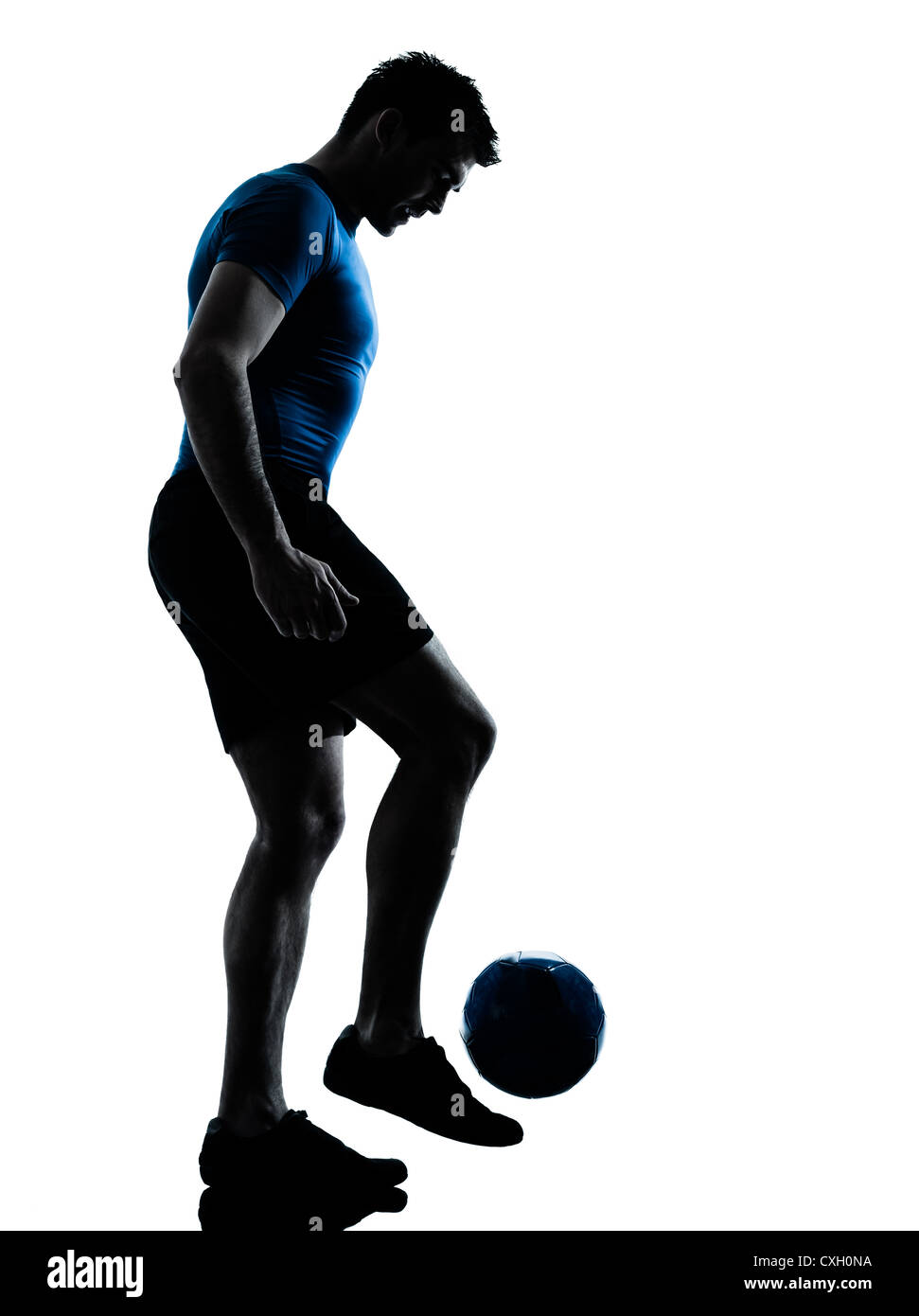 one caucasian man playing soccer juggling football player silhouette  in studio isolated on white background - Stock Image