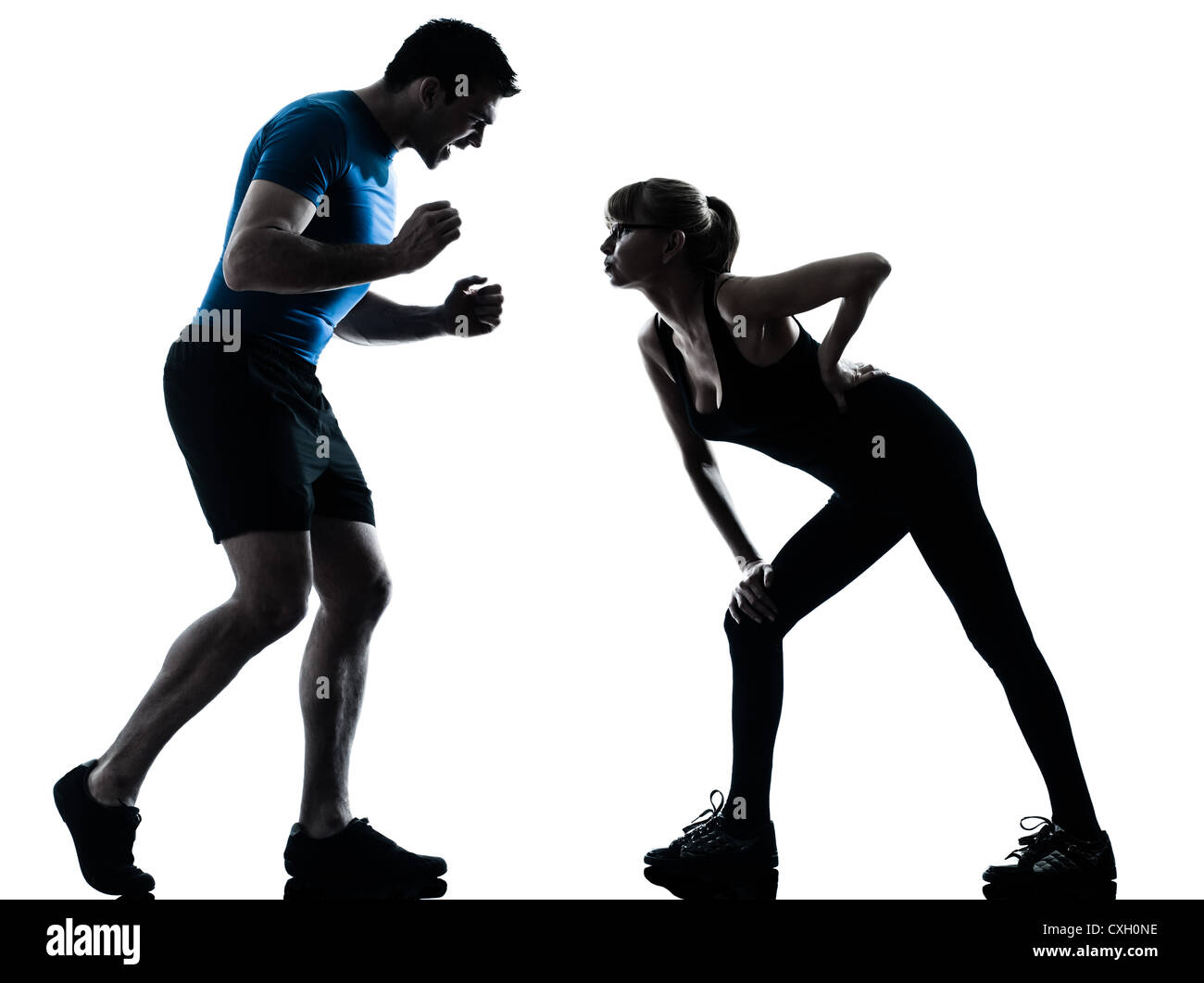 caucasian aerobics instructor  with mature woman exercising fitness workout in silhouette studio isolated on white - Stock Image