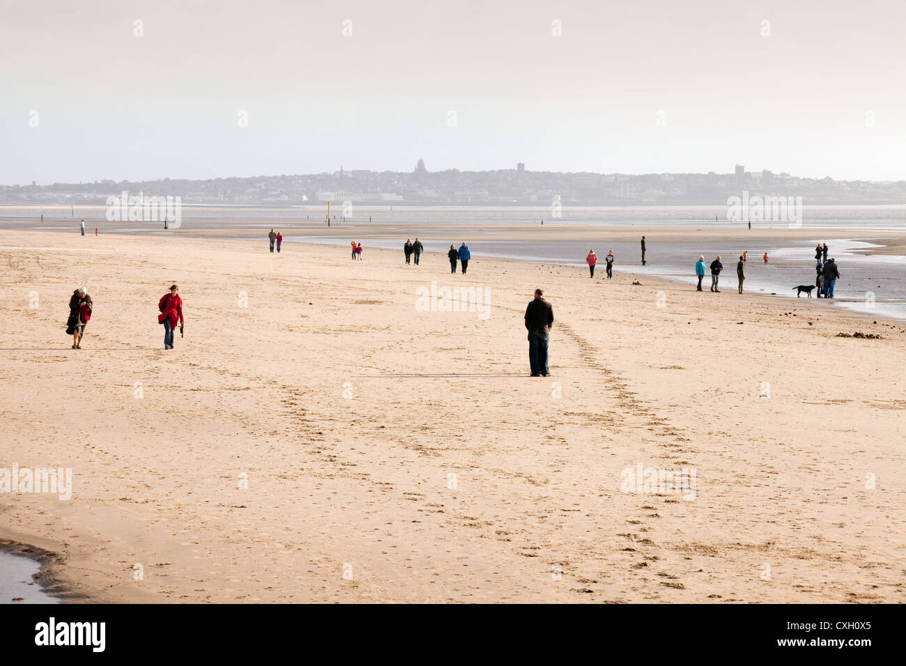 View of people on Crosby beach in the evening, Liverpool, Merseyside Lancashire UK - Stock Image
