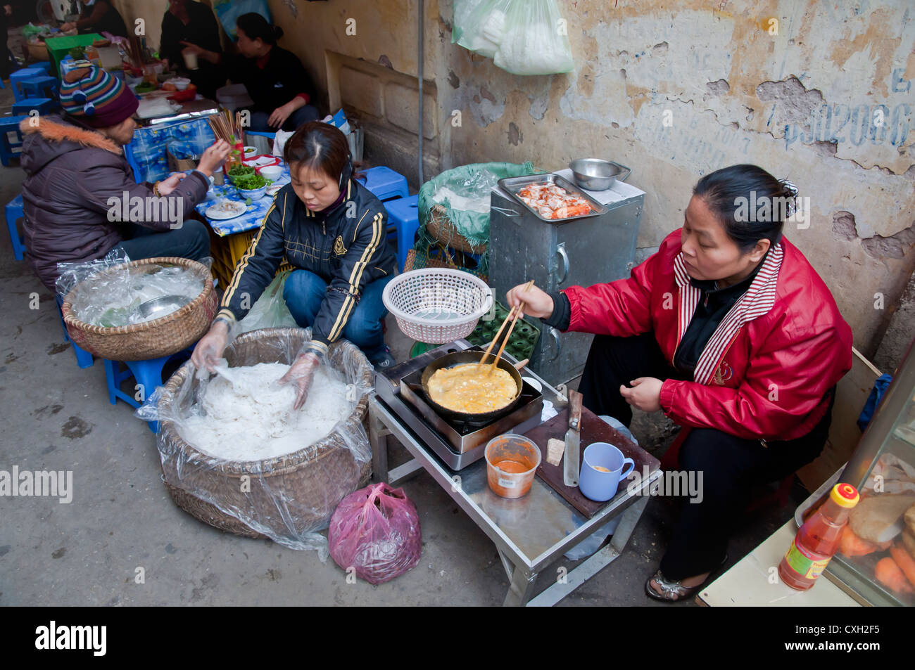 Woman frying egg for a street food breakfast, Hanoi Stock Photo