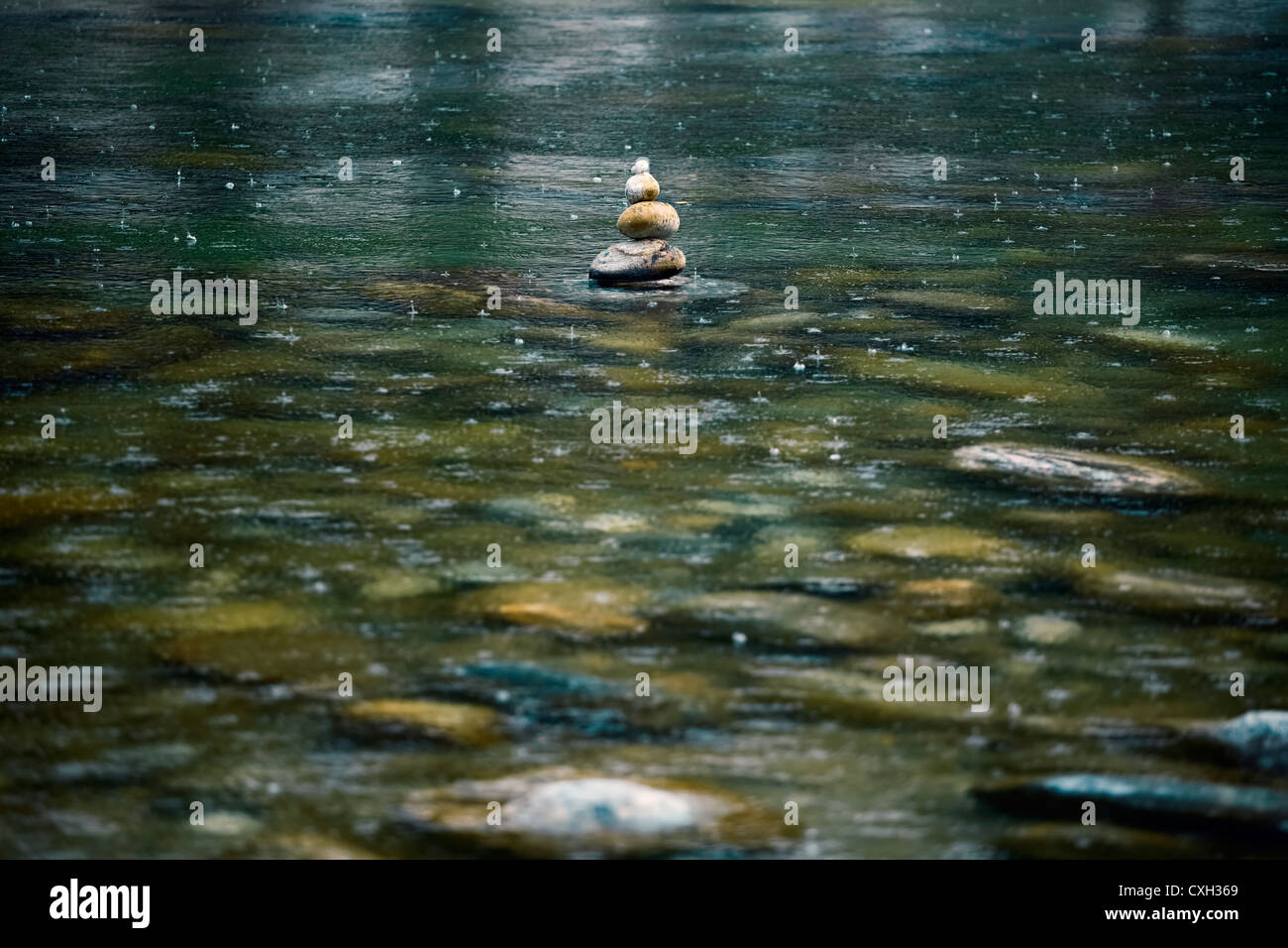 Stone tower in a river bed in the rain - Stock Image