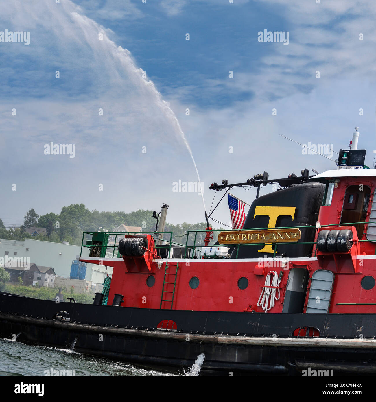 Bright red tugboat Patricia Ann gives the OpSail 2012 participants a fire fighting salute in New London Connecticut - Stock Image