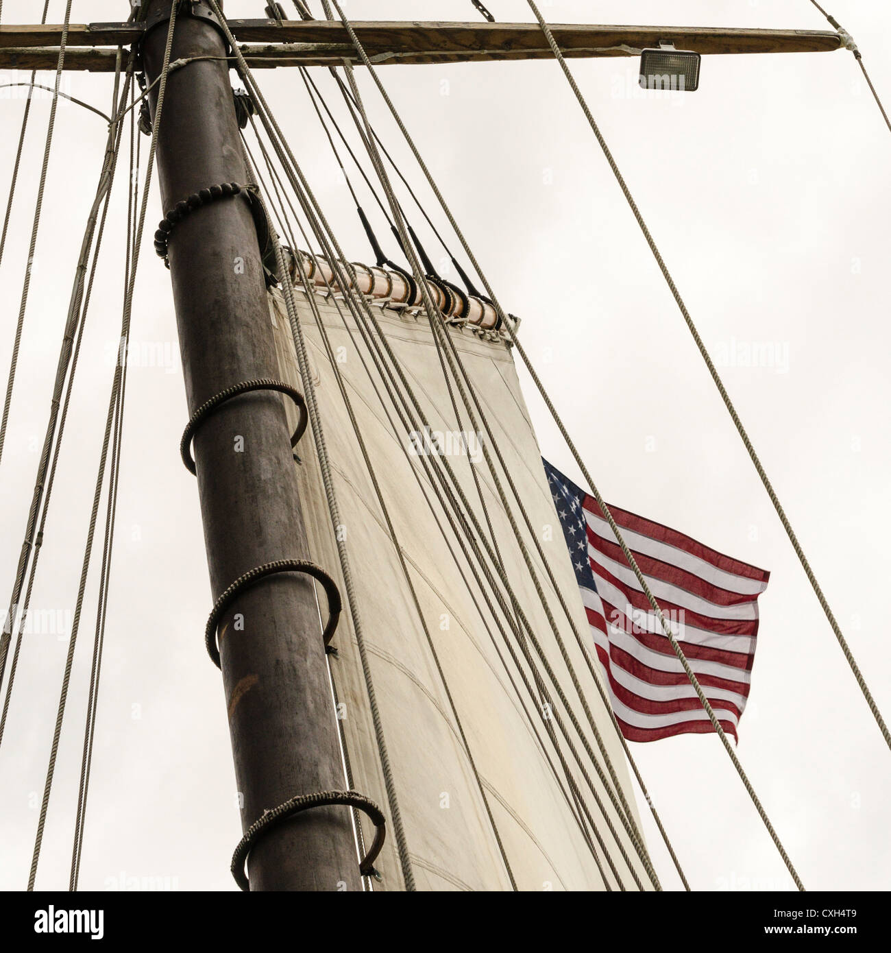 An American flag flies from the mast of the tall ship schooner Tyrone from Cape Cod at the start of OpSail Connecticut - Stock Image