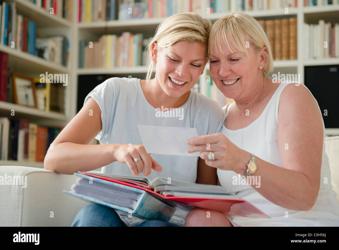 Family happiness and memories, happy mom and daughter looking at pictures in photo album - Stock Image