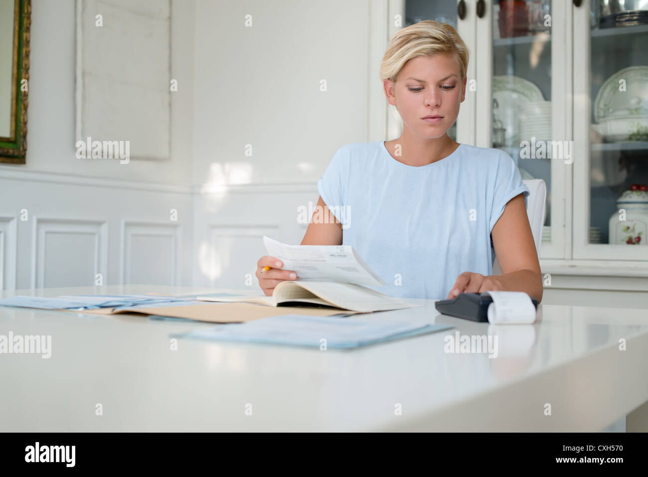 young blond woman checking bills and using calculator at home Stock Photo