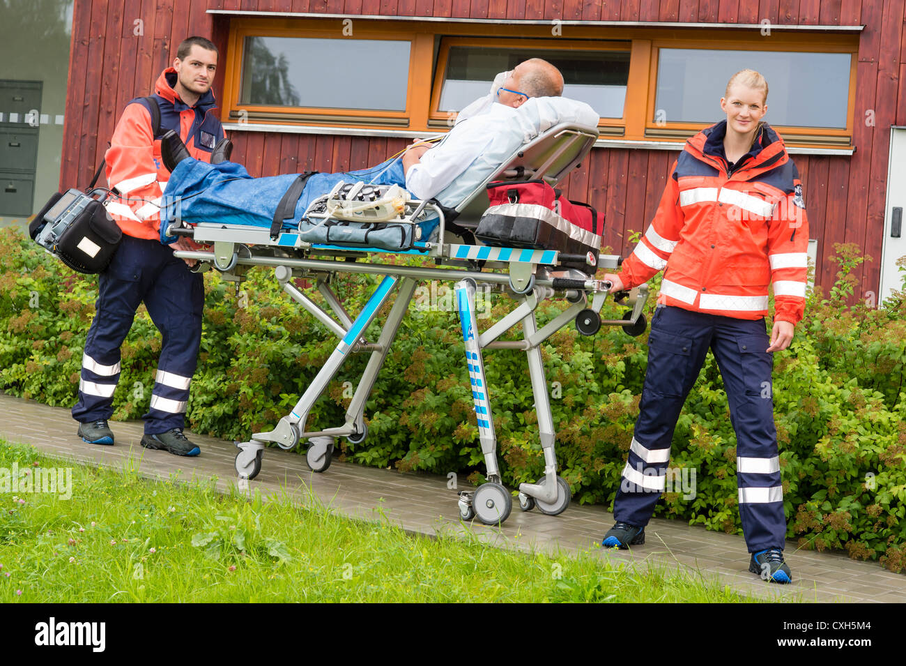 Paramedics with patient on emergency stretcher ambulance aid woman man - Stock Image