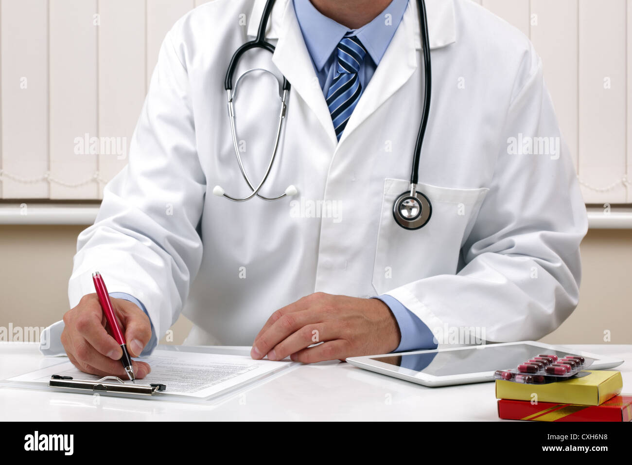Doctor writing a prescription or medical examination notes - Stock Image