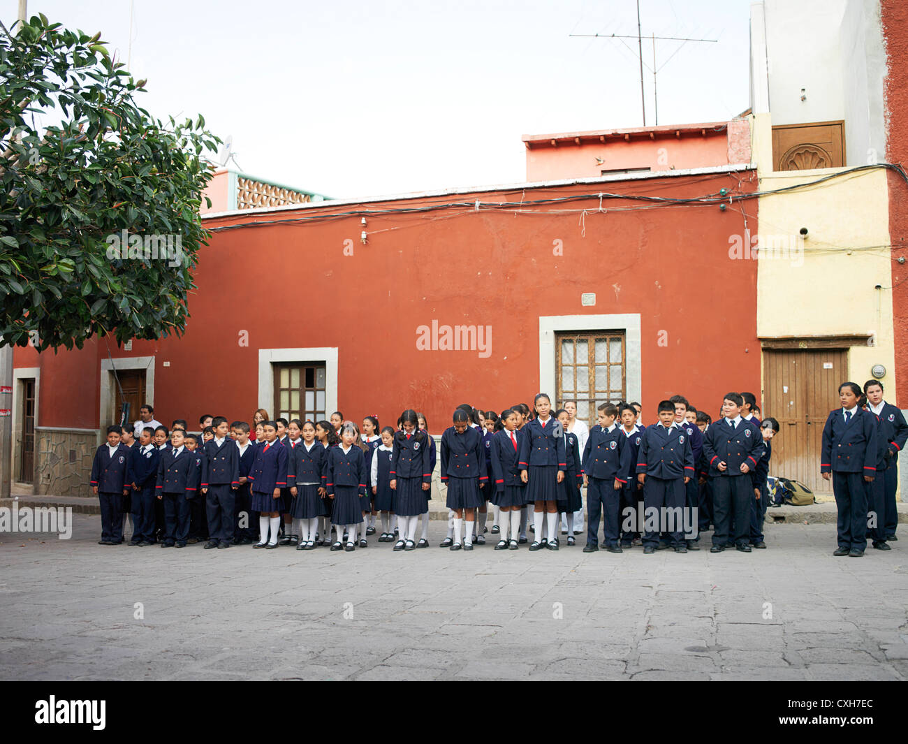 A group of young Mexican school children all line up outside - Stock Image