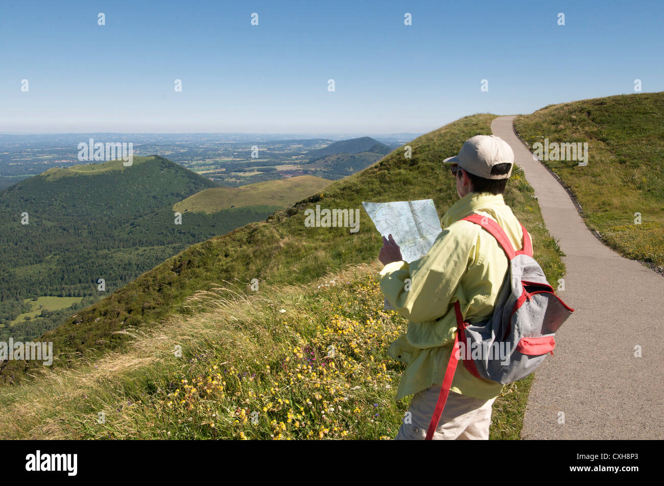 Hiker on the Puy de Dome looking at the volcanic landscape of the Chaine des Puys, Auvergne, France - Stock Image
