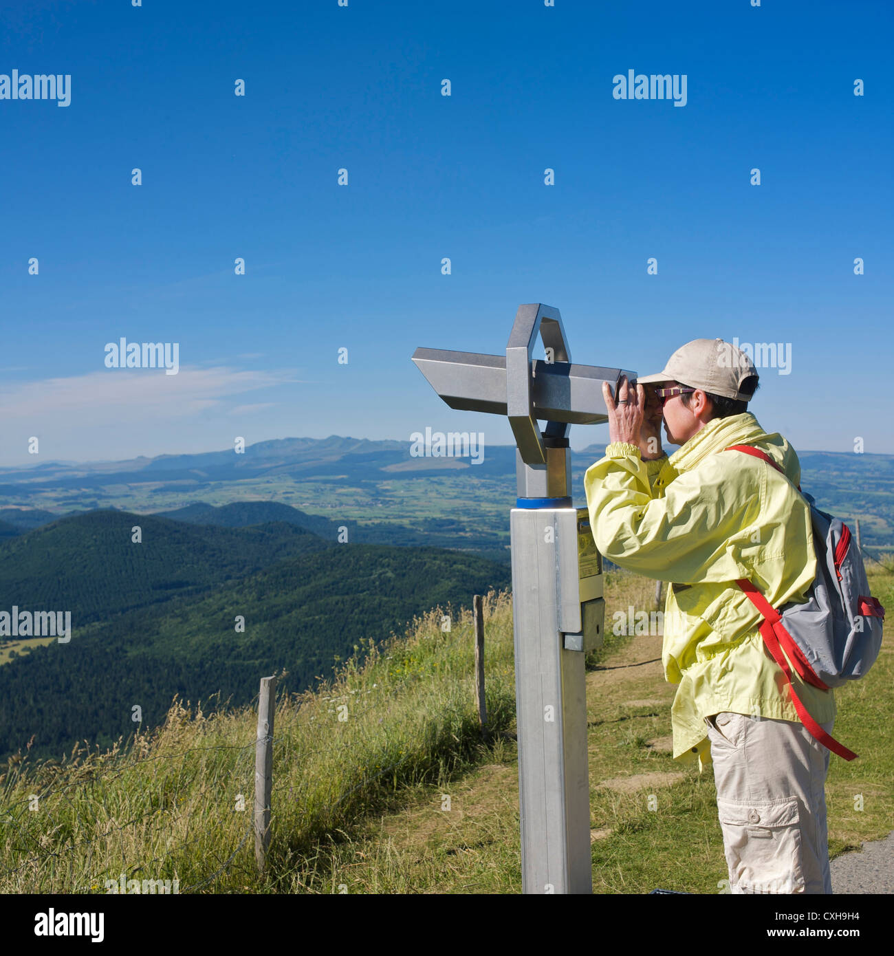Hiker looking through a binocular a mountain landscape. Regional Park of Auvergne volcanoes. France. - Stock Image
