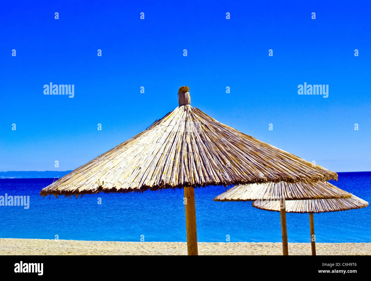 A straw umbrella on a tropical beach with blue sky - Stock Image