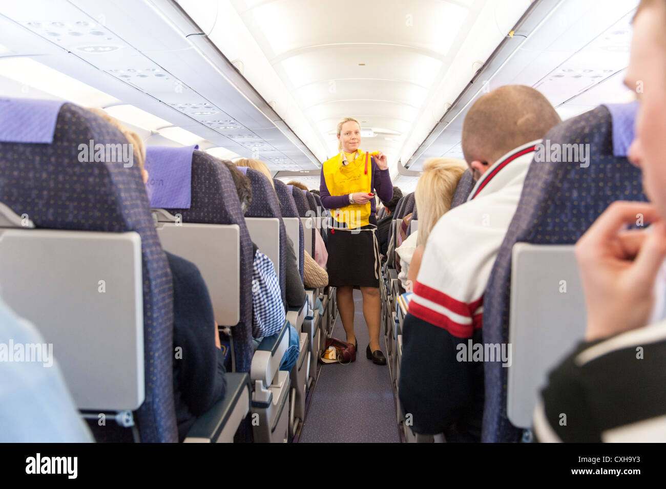 Monarch Airlines air stewardess going through preflight safety demonstration, England, UK - Stock Image