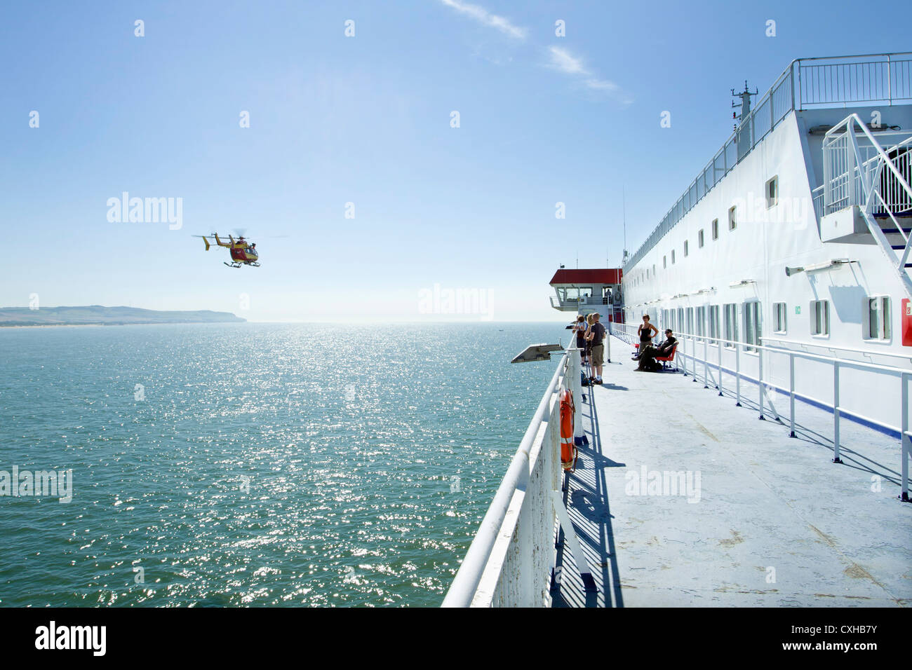 Civil protection French helicopter flies alongside a passenger ferry leaving Calais in France - Stock Image