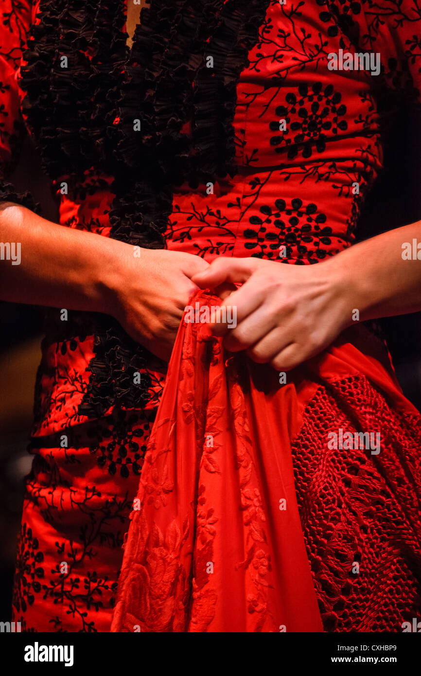 Detail of a traditional Flamenco dancer red dress costume embroidery and shawl in Seville, Spain - Stock Image