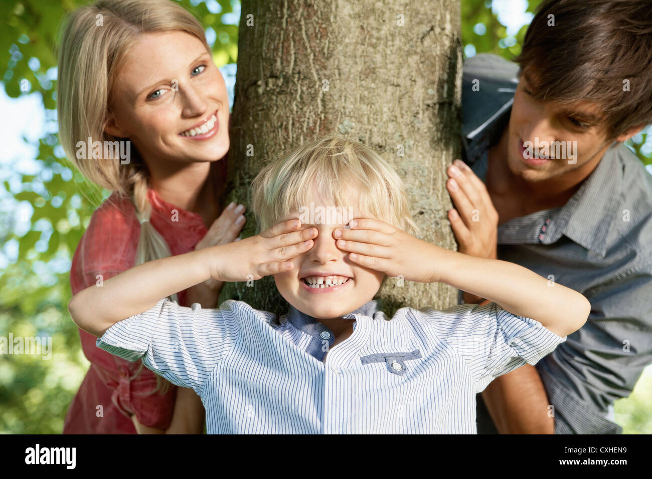 Germany, Cologne, Boy playing hide and seek with parents - Stock Image