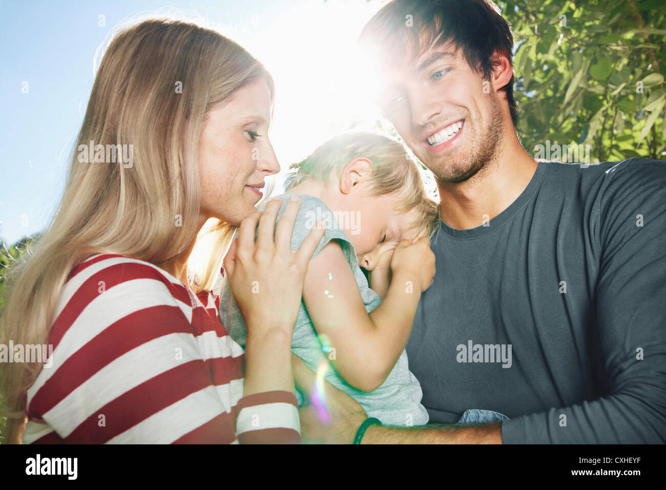 Germany, Cologne, Parents carrying tired son, close up - Stock Image