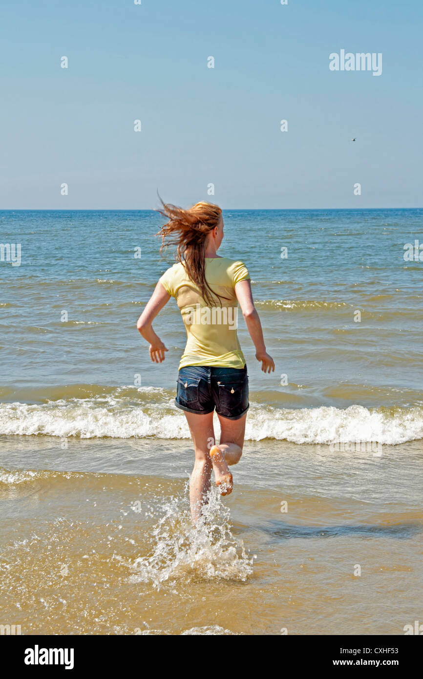 Young woman running into the water from the north sea in the Netherlands - Stock Image