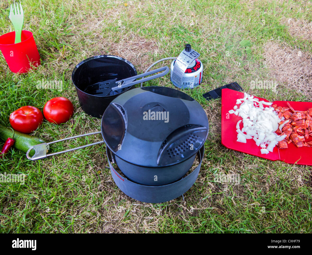 Meal being prepared while camping on small stove and cutting board - Stock Image
