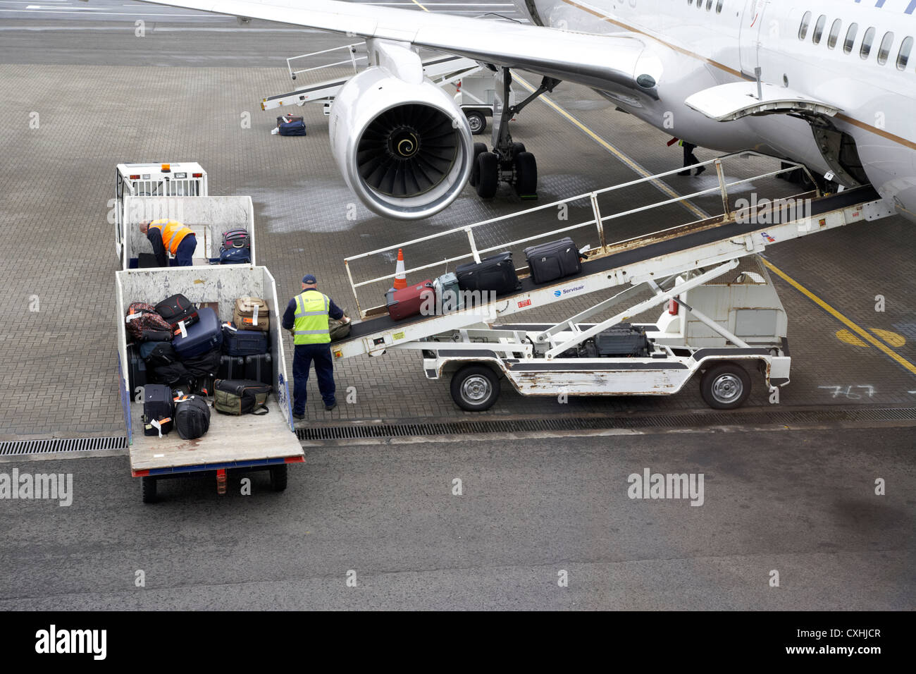 baggage handlers loading United Airlines Boeing 757 at Belfast International Airport - Stock Image