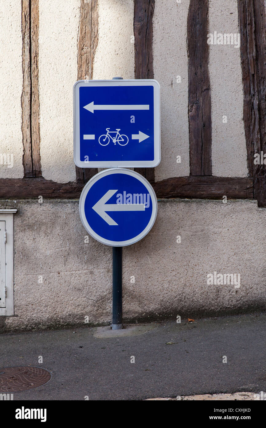 Confusing cycle lane and traffic signs with arrows in Chartres, Loire, France - Stock Image