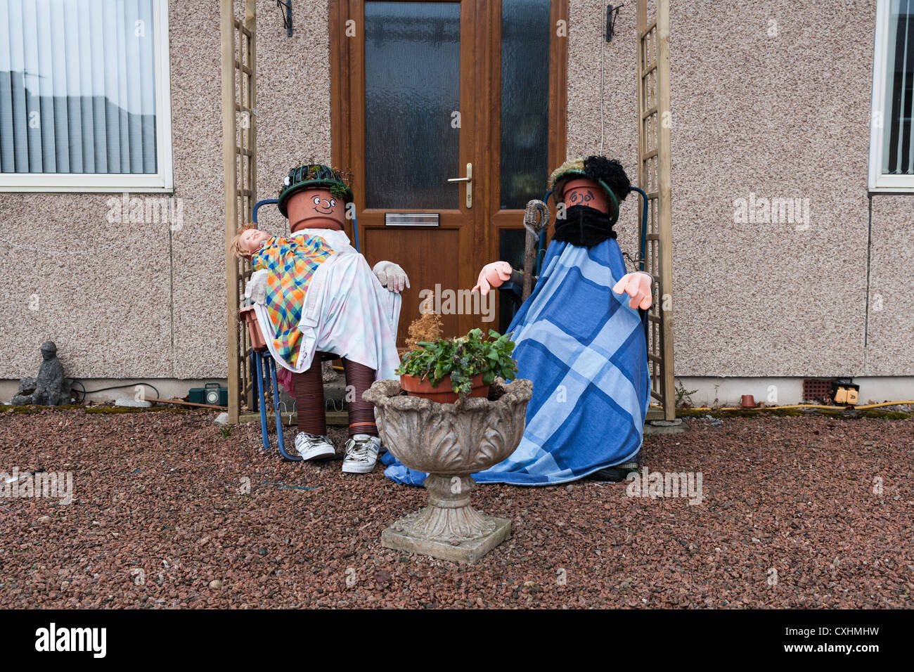 Two plant pot people sitting outside their house. - Stock Image