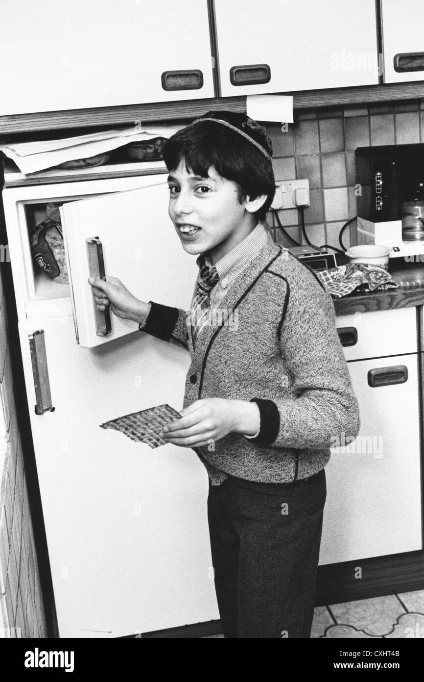 Child finding the afikoman hidden matzo part of the feast of the Passover service in a Jewish family home 1980s - Stock Image