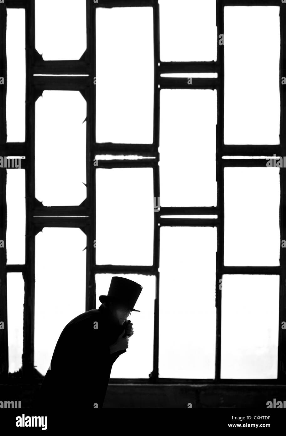 Silhouette of the Man in the black coat and hat in the dark interior near the meshed window Stock Photo