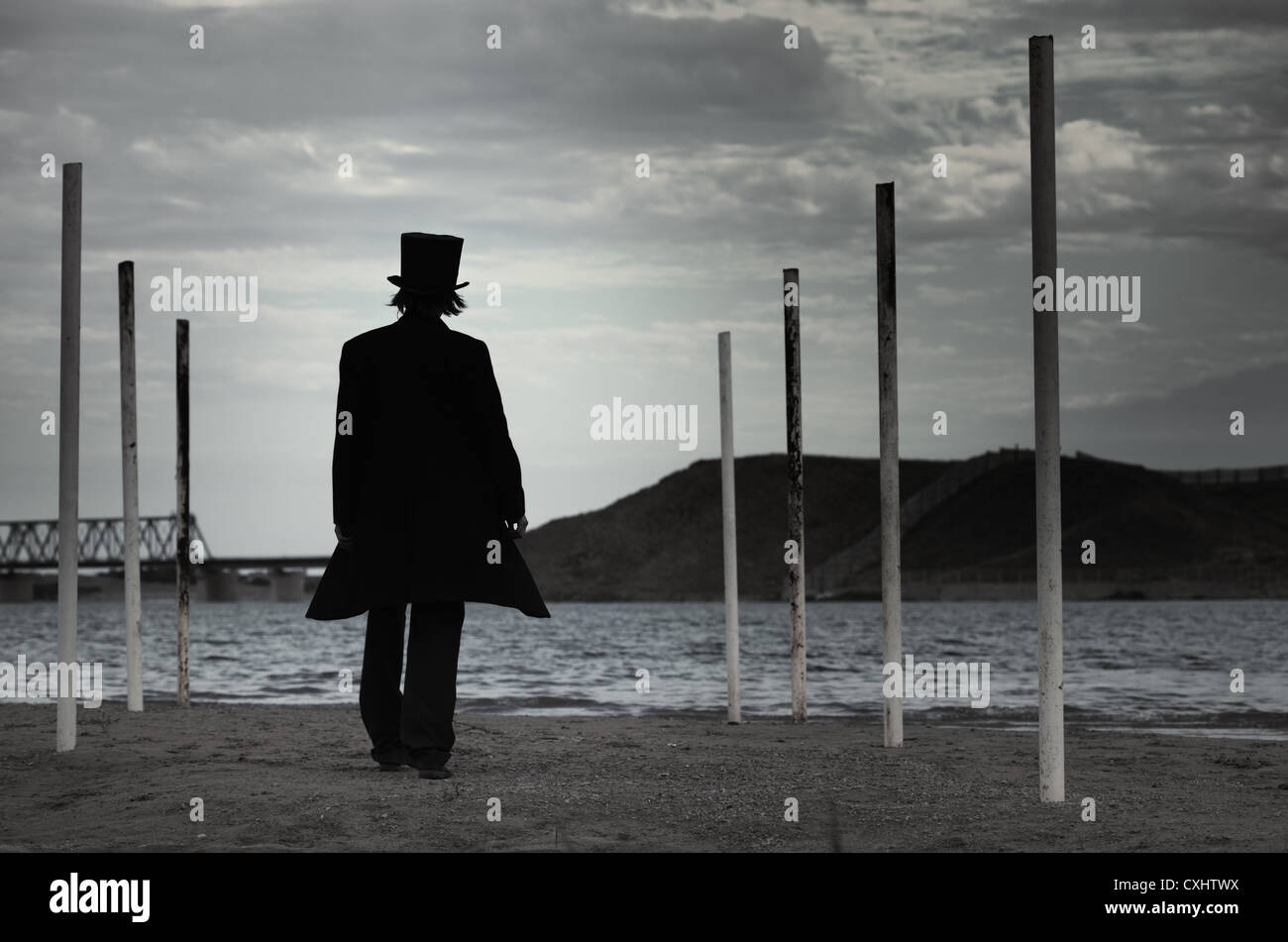 Rear view on alone man in the black coat and top-hat going to the sea. Natural darkness. Artistic colors added - Stock Image