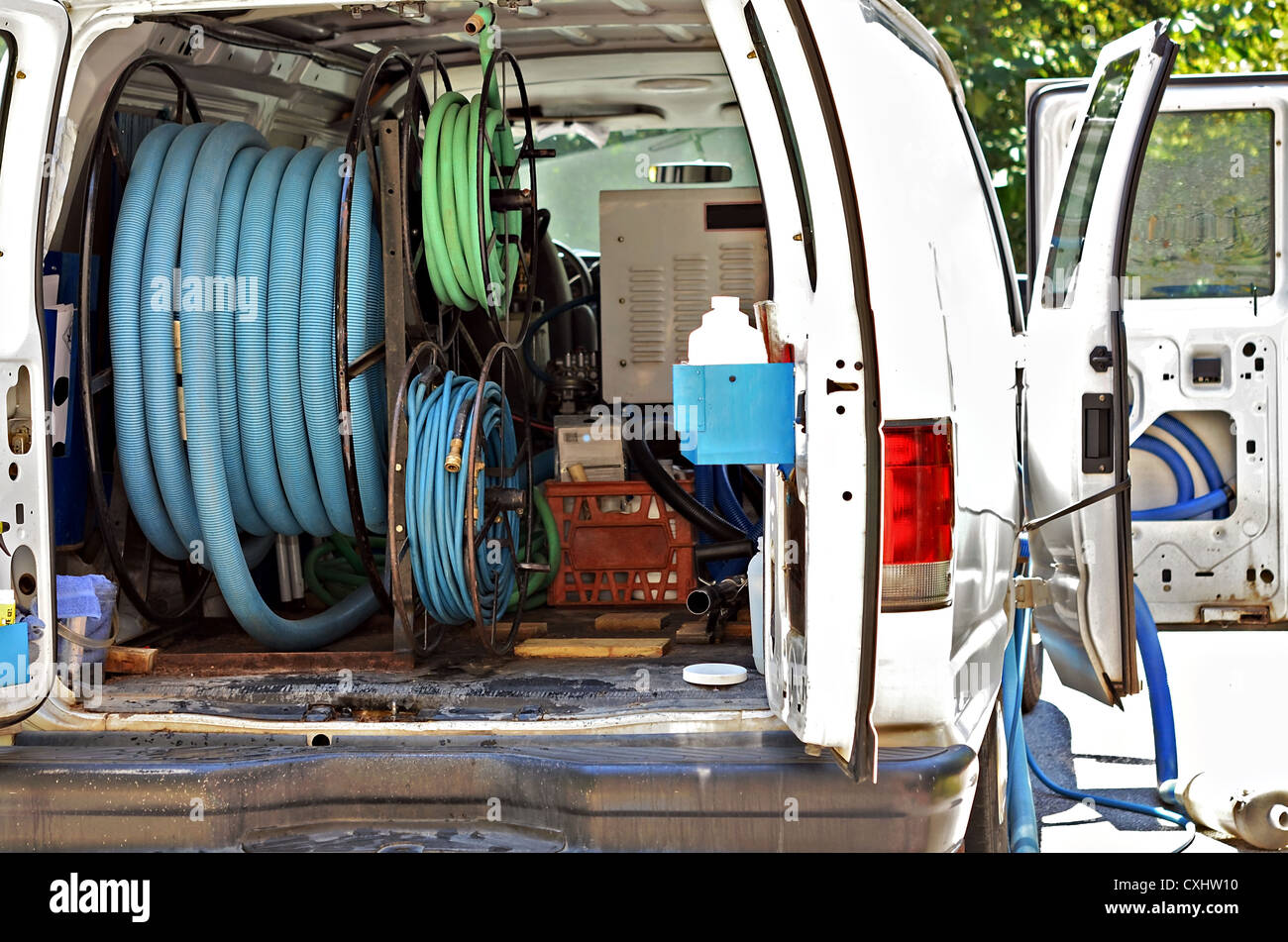 A white van with hoses and equipment for carpet cleaning. - Stock Image