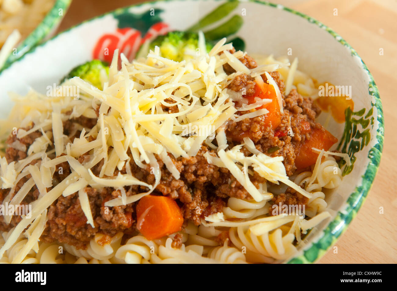 Bowl of pasta and meat sauce topped with grated cheese. - Stock Image