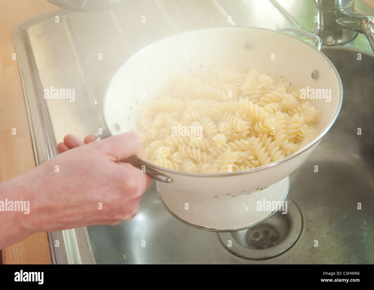 Steam rising from pasta being drained in a colander over a kitchen sink. - Stock Image