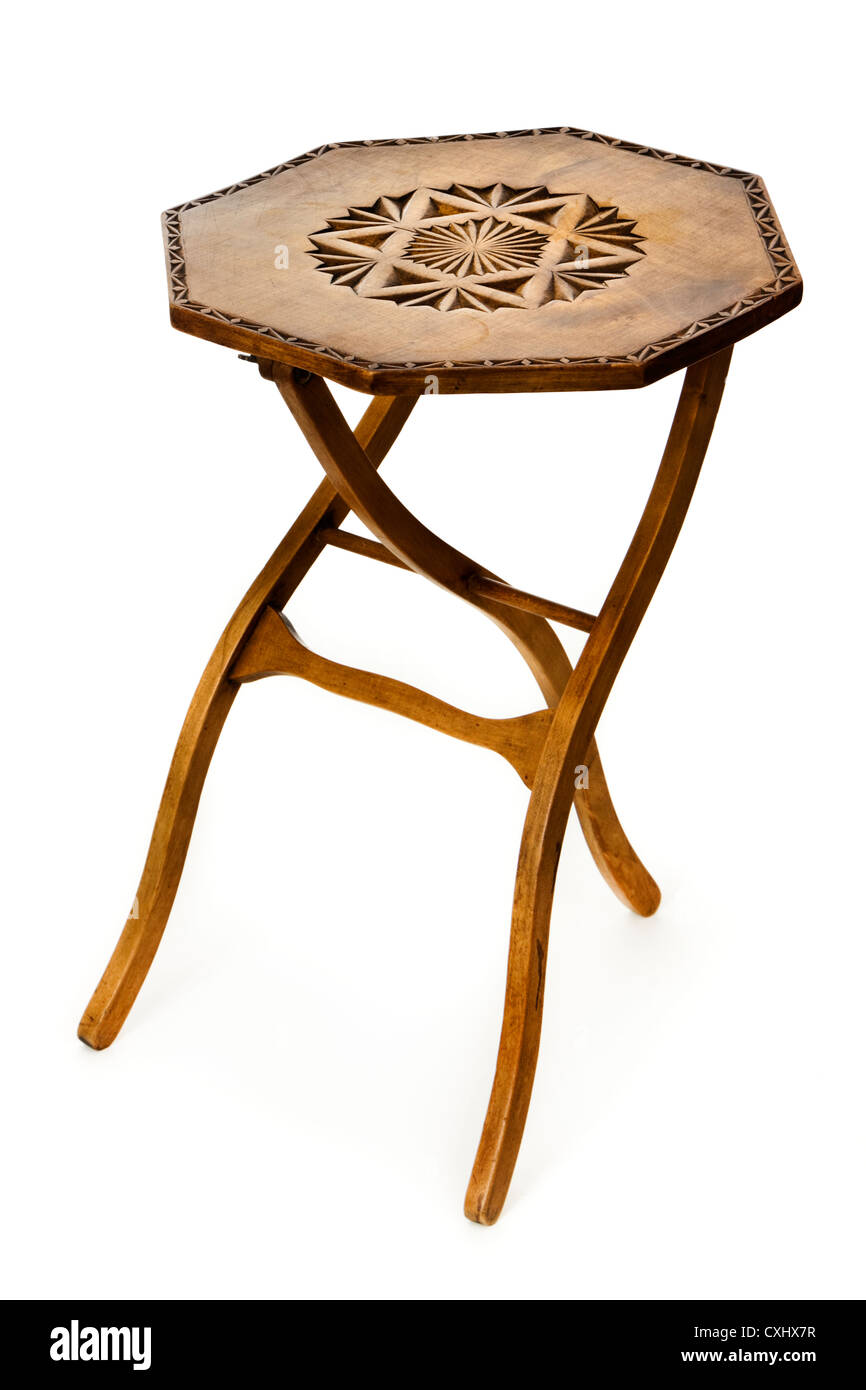 Vintage folding three-legged wooden coffee / side table with carved top - Stock Image