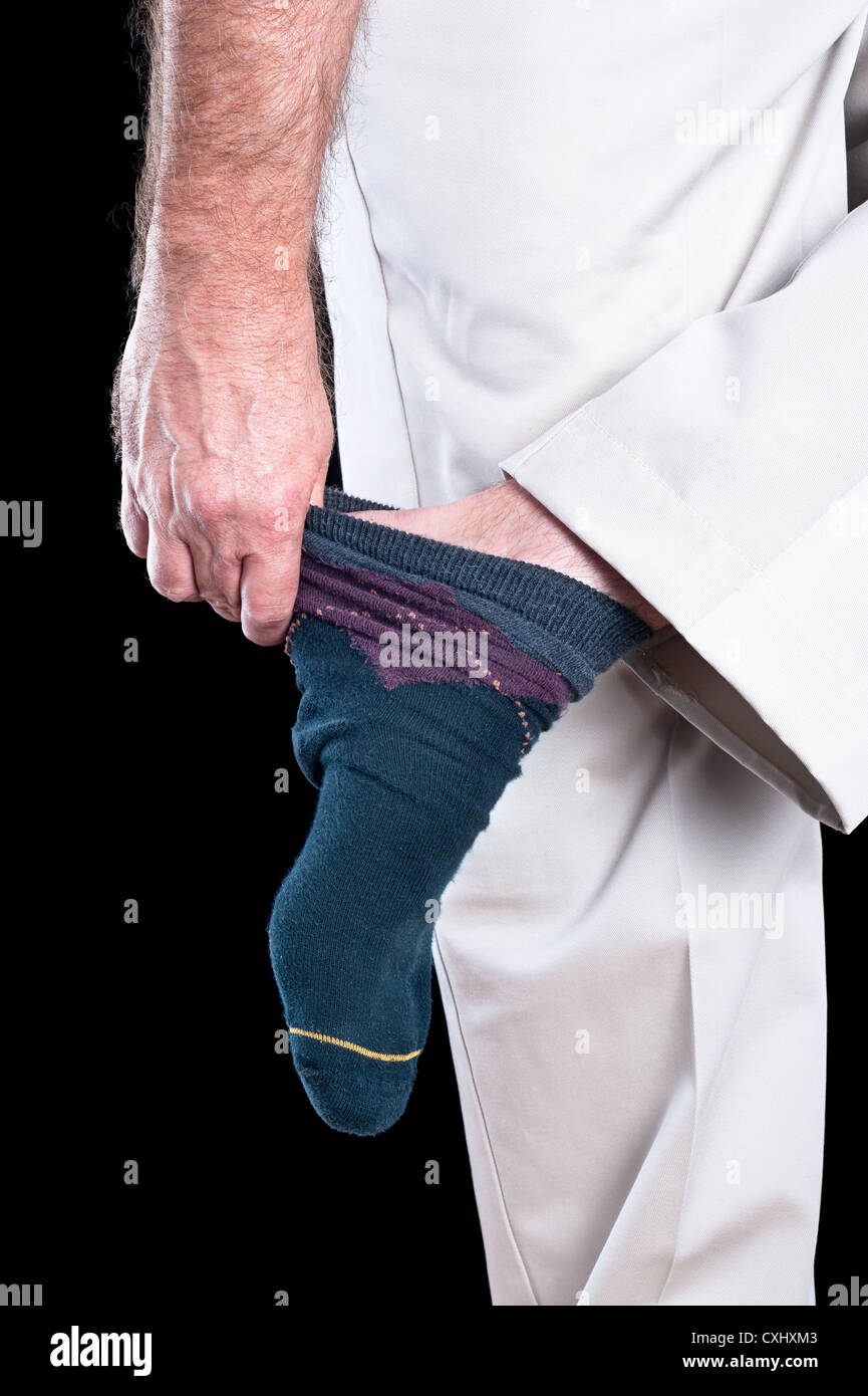 A man removing his socks shows several inferences regarding dexterity and daily tasks adults conduct. - Stock Image