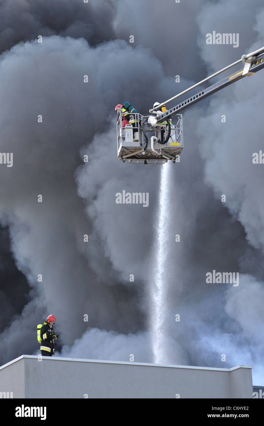 Firefighters extinguish a raging fire. - Stock Image
