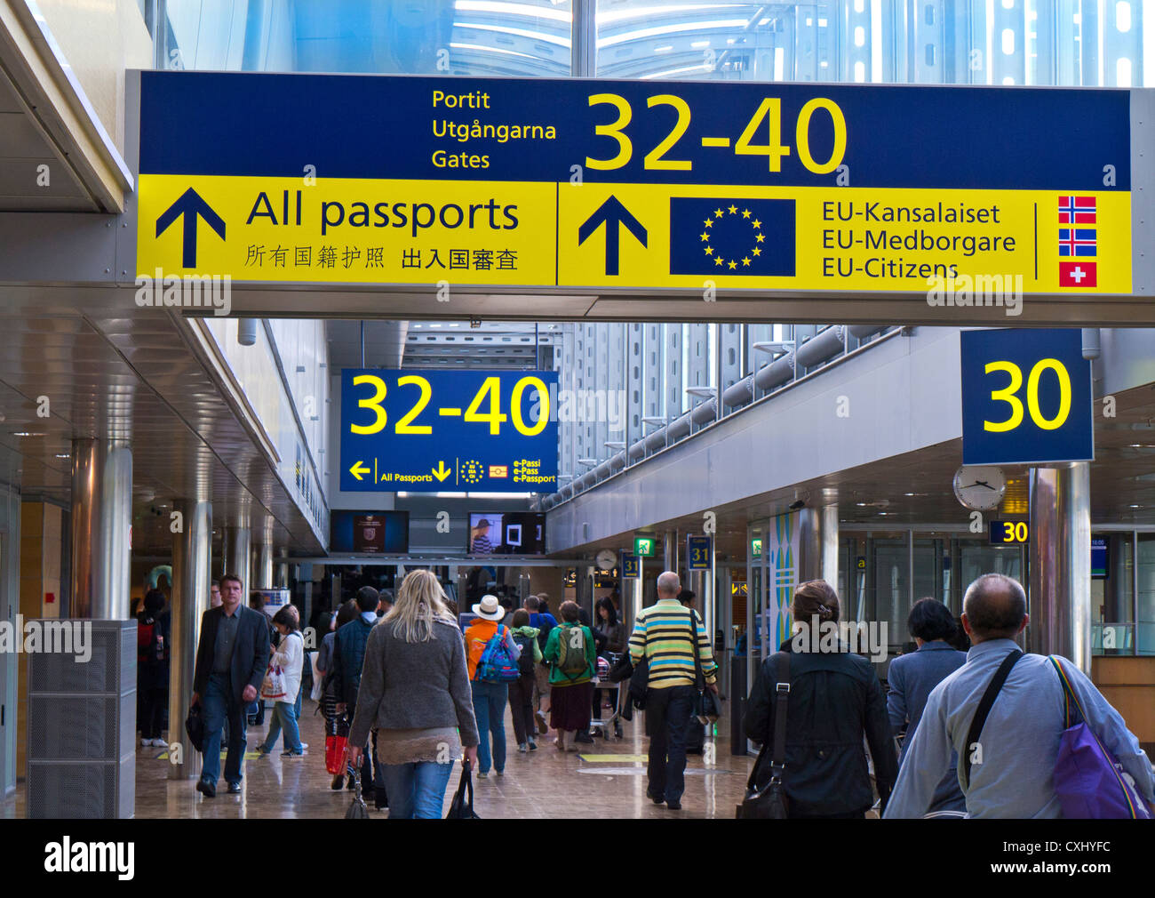 Airport Passengers airside on concourse to border control and departure boarding gates at Vantaa Helsinki airport - Stock Image