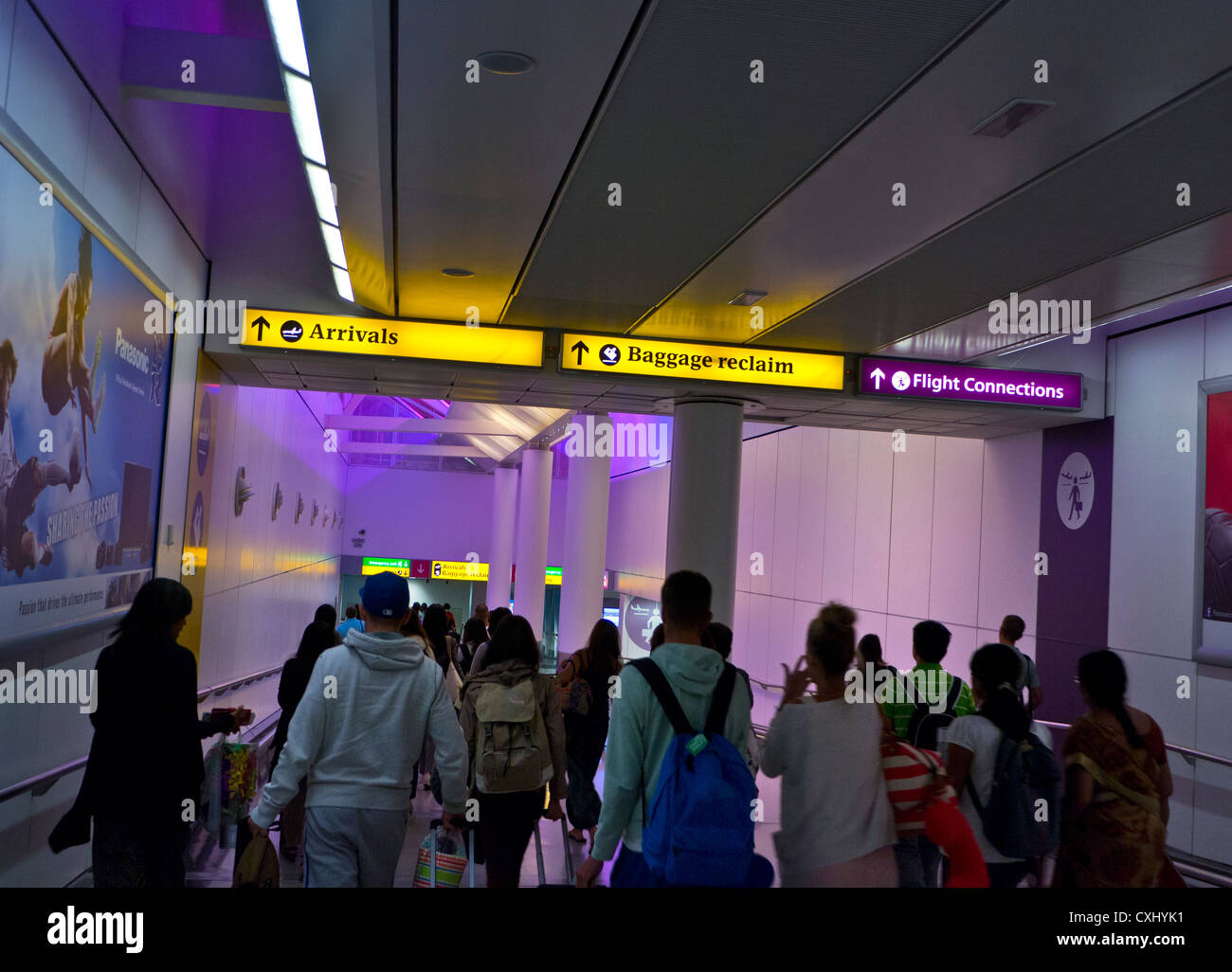 Airline passengers arriving at  Heathrow airport lit by calming suffused colours heading for arrivals and baggage - Stock Image