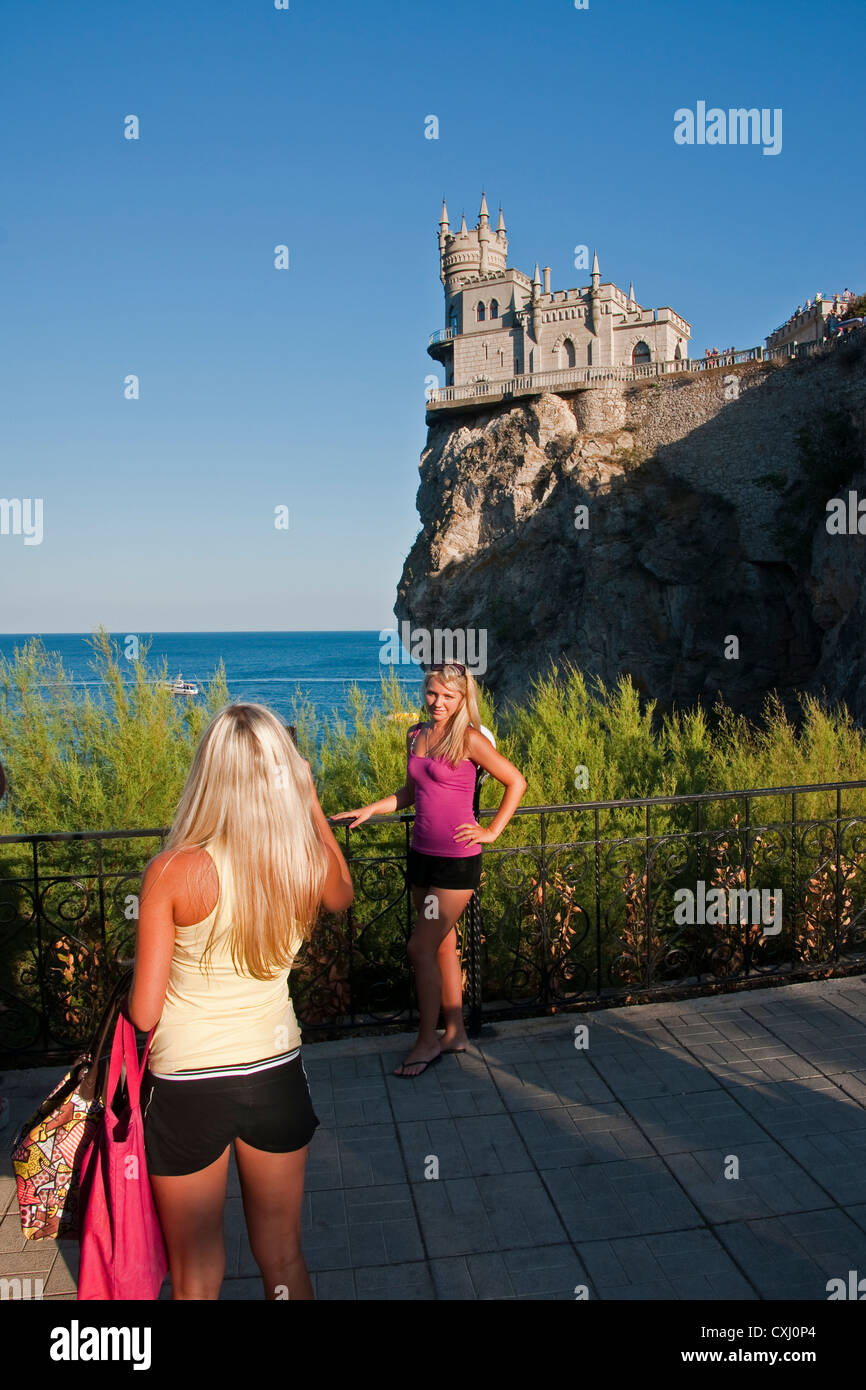 Ukrainian tourists taking photos at Swallow's Nest Castle overlooking the Black Sea near Yalta. - Stock Image