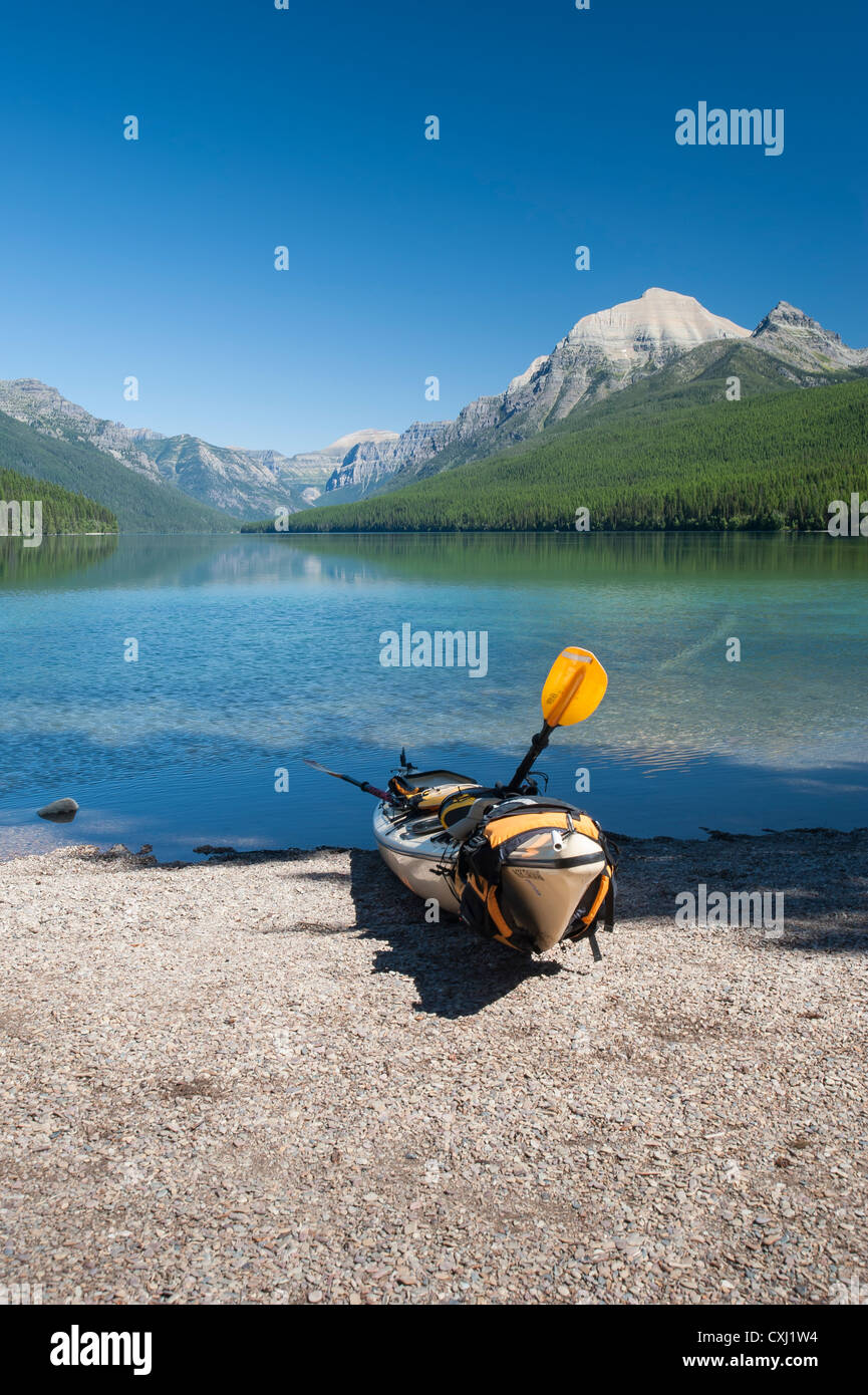 Yellow kayak sits on the shore of Bowman Lake in Glacier National Park, Montana. - Stock Image
