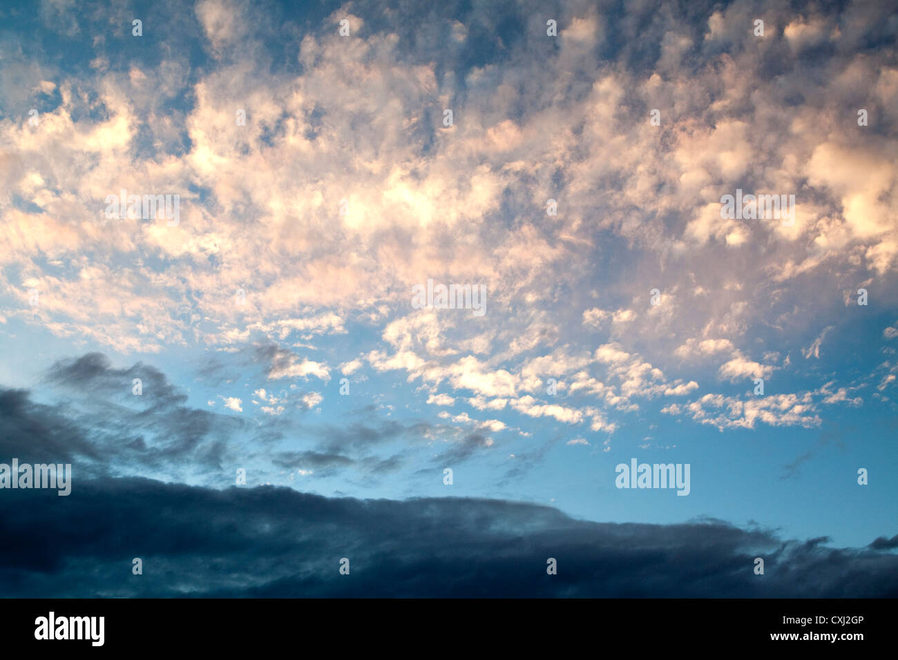 Altocumulus clouds with dark stratus cloud beneath near sunset Stock Photo