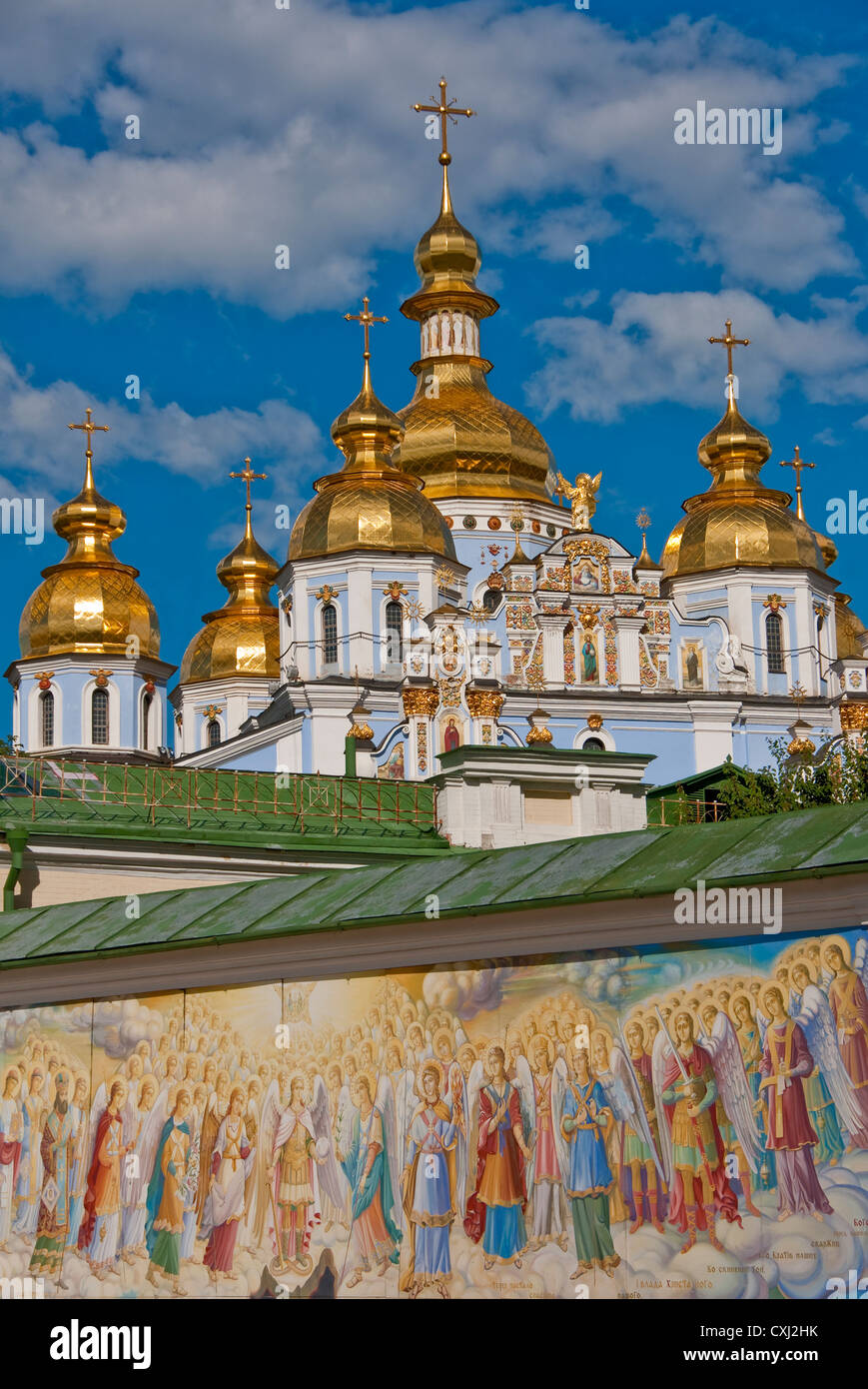 Golden-domed St. Michael's Cathedral in Kiev with mural on wall in foreground. - Stock Image