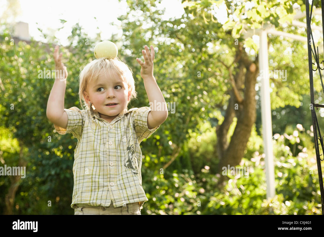 Germany, Bavaria, Boy playing with apple on top of head - Stock Image