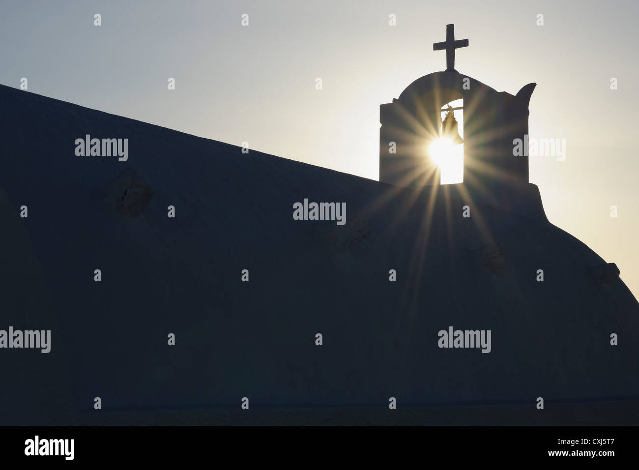Greece, Sun shines through belltower in Oia village at Santorini - Stock Image