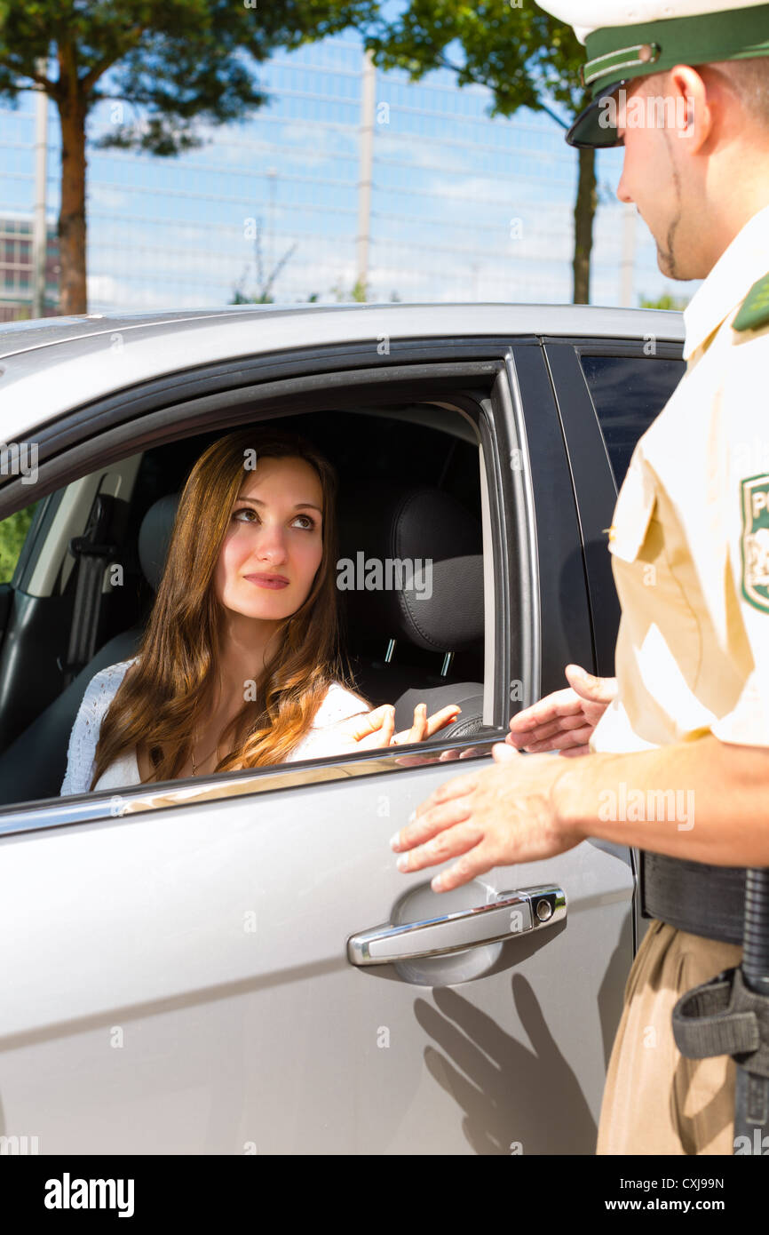 Police - young woman with policeman or cop on the street or traffic - Stock Image