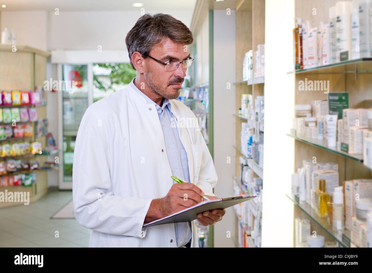 Germany, Brandenburg, Pharmacist checking products in pharmacy - Stock Image