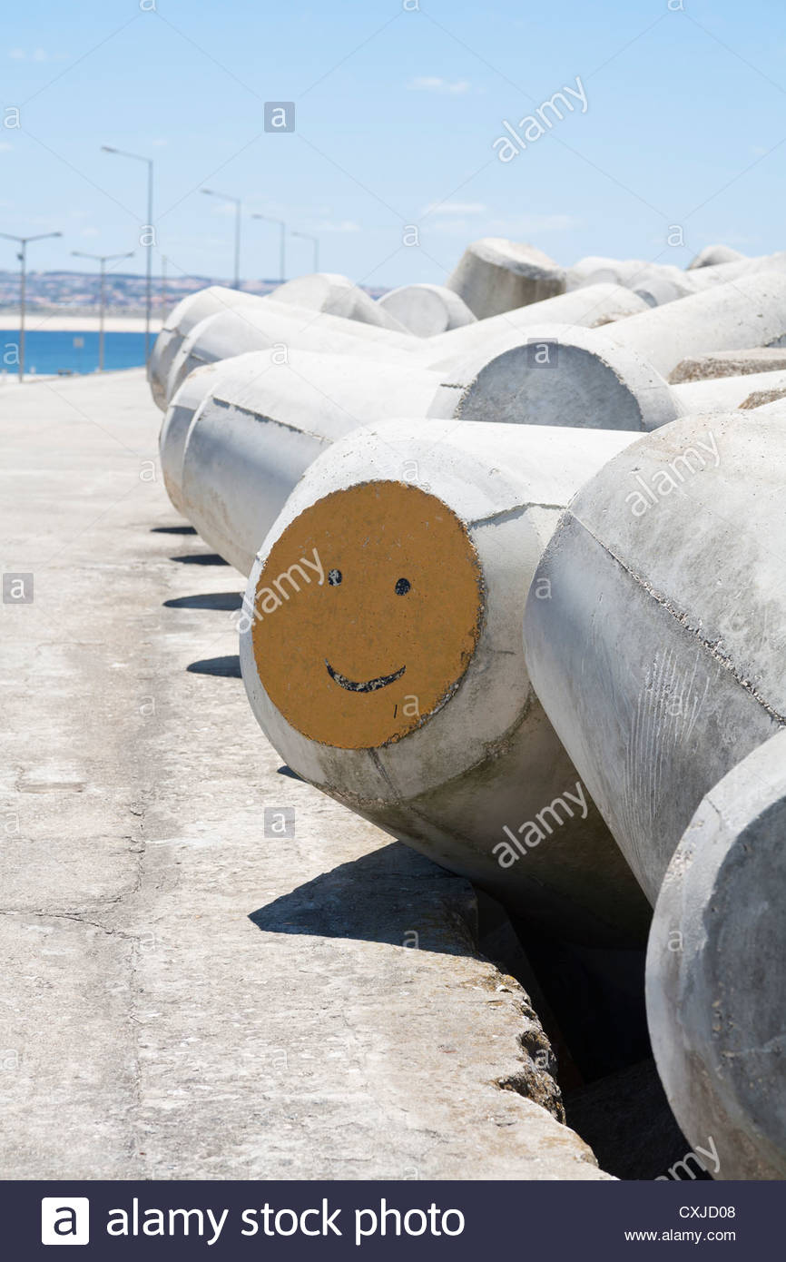 Concrete tetrapod beach defense in Peniche, Portugal with smiley face graffiti - Stock Image