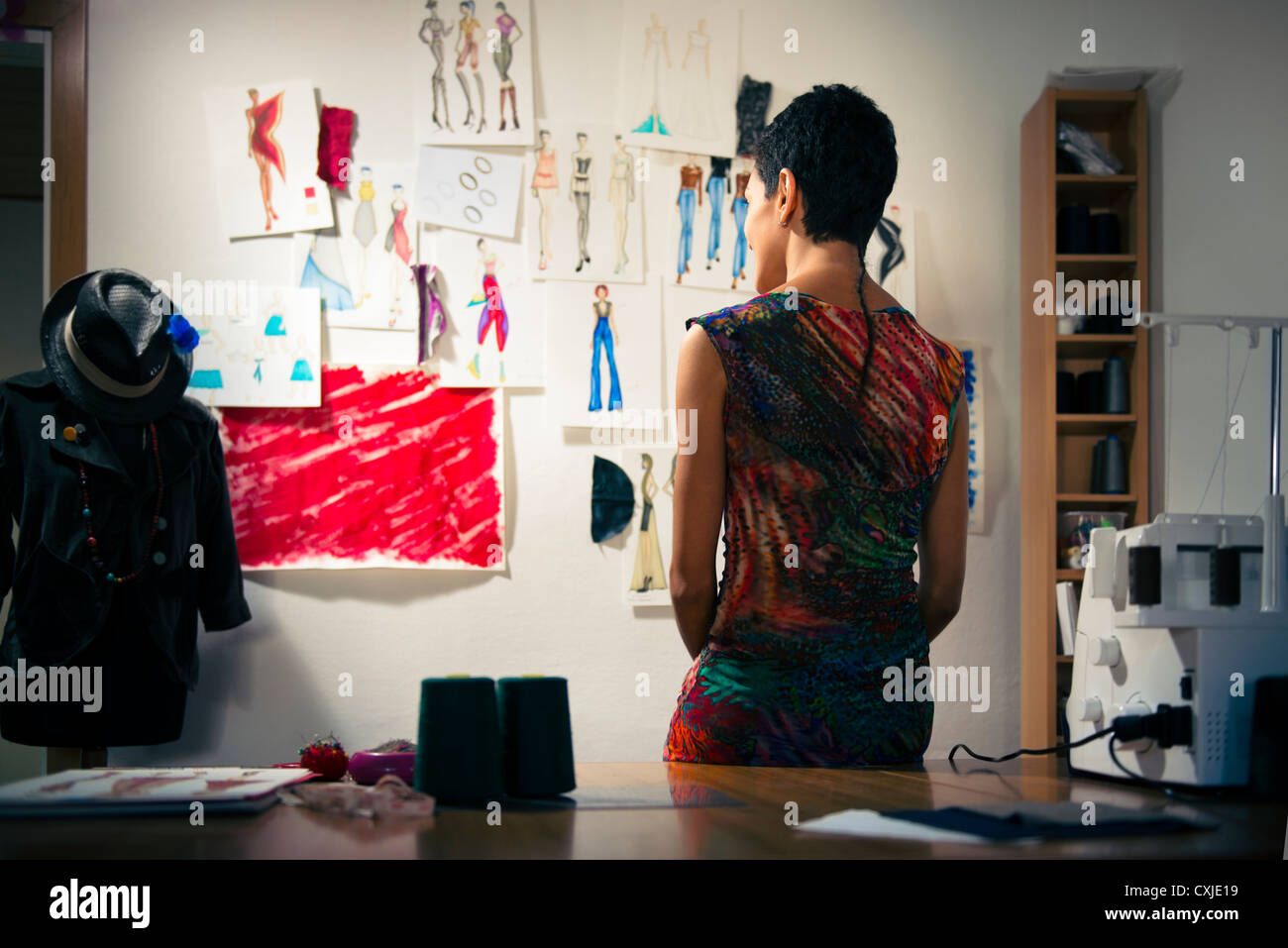 Confident entrepreneur, hispanic young woman working as fashion designer and dressmaker in atelier - Stock Image