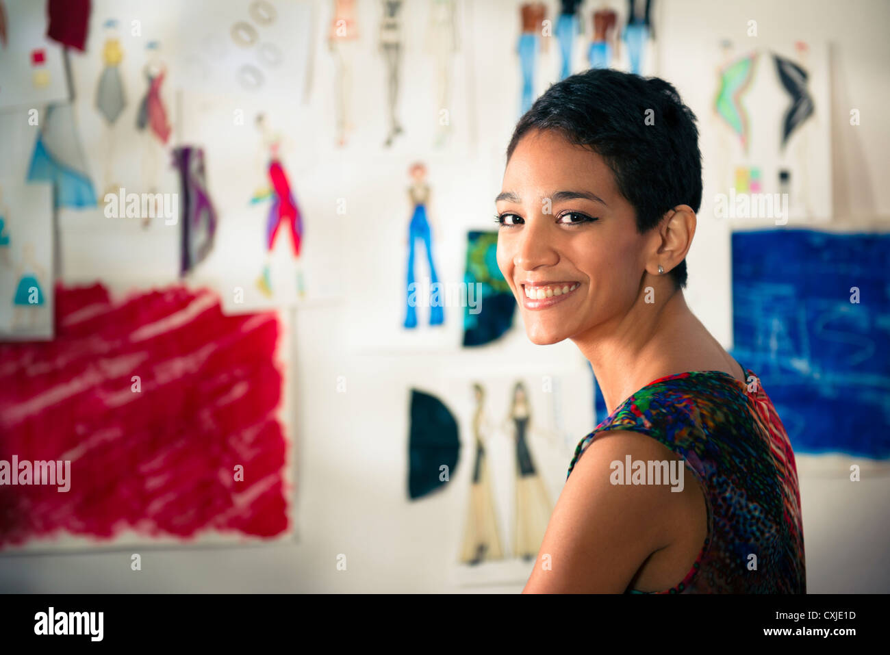 Confident entrepreneur, portrait of happy hispanic young woman working as fashion designer and dressmaker in atelier - Stock Image