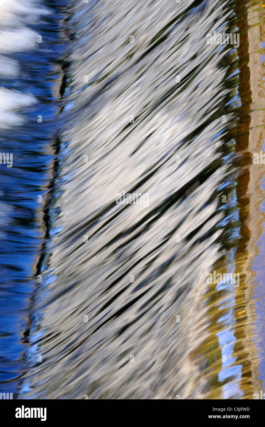 Pattern of colorful reflections on a weir in the Water of Leith, Edinburgh - Stock Image