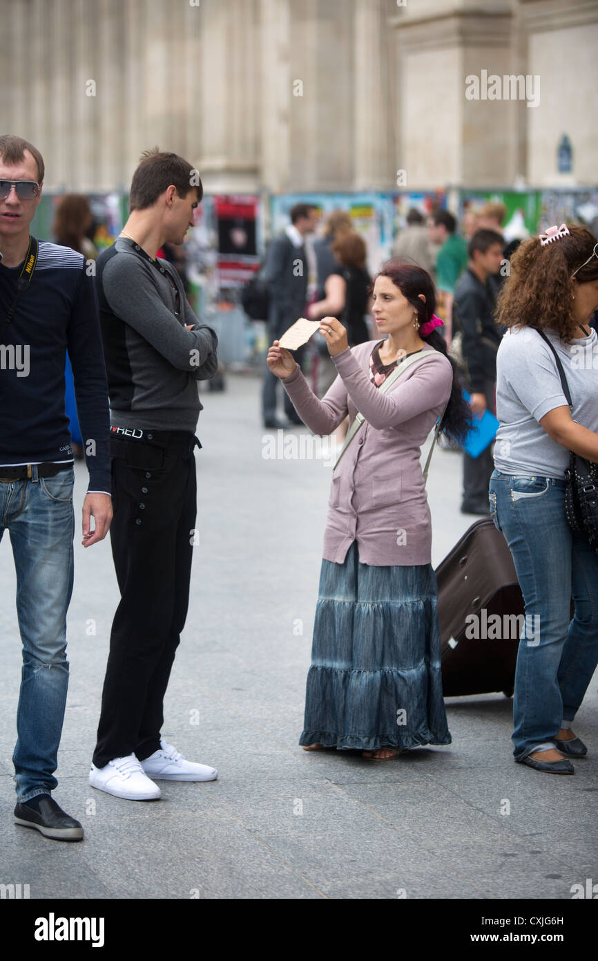 A Romani gypsy outside SNCF Paris Gare du Nord railway station in France, holds a hand-written card to a passenger - Stock Image