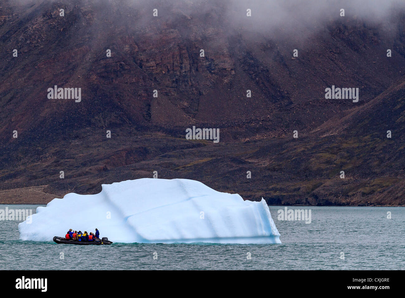 Zodiac boat with tourists coasts by small iceberg in Nunavut, Canada. Summer, high arctic. - Stock Image